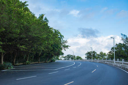 asphalt road under the blue sky and white clouds Stock Photo