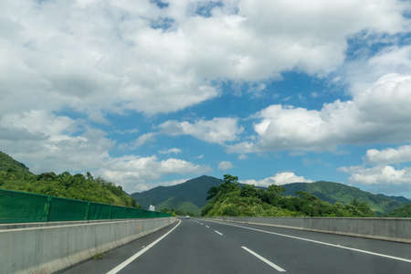 Highway under blue sky and white clouds