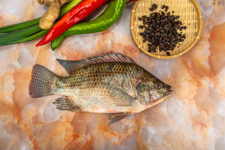 A strip of tilapia and ingredients on marble table 免版税图像