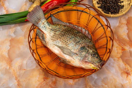 Basket of fresh tilapia with ingredients