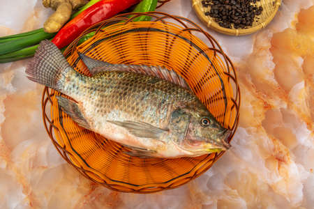 A tilapia in the basket with ingredients 免版税图像