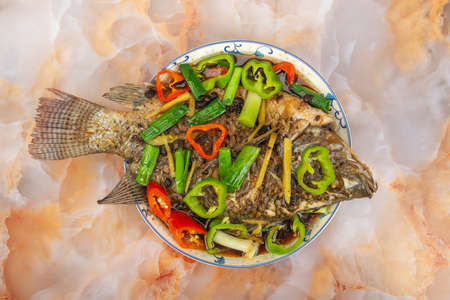 A plate of steamed tilapia on marble table