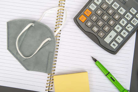 Masks and office supplies on the notebook