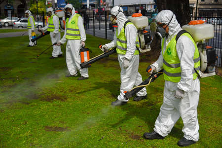 fumigador: Buenos Aires, Argentina - March 3, 2016: Employees of the Ministry of Environment and Public Space fumigate for Aedes aegypti mosquitos to prevent the spread of zika virus and Dengue fever in park.
