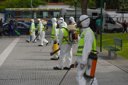 gasmask: Buenos Aires, Argentina - March 3, 2016: Employees of the Ministry of Environment and Public Space fumigate for Aedes aegypti mosquitos to prevent the spread of zika virus and Dengue fever in park.