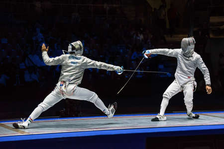 fencers: Moscow, Russia - May 30, 2015: Unidentified professional fencers in the finals of the mens individual event at the 2015 Moscow Sabre international fencing tournament.