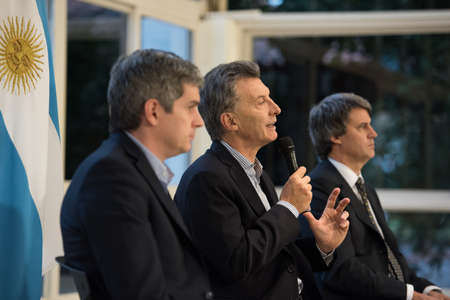 political economist: Olivos, Argentina - May 6, 2016: President of Argentina Mauricio Macri (C), Finance Minister Alfonso Prat-Gay (R) and Cabinet Chief Marcos Pena during a press conference at the presidential residence Editorial