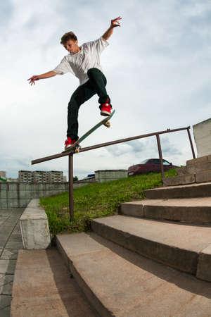 grind: Zelenograd, Russia - July 29, 2009: Skateboarder Nikita Shumkov doing a backside crooked grind trick on a handrail in Zelenograd, Russia.