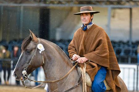 Buenos Aires, Argentina - Jul 16, 2016: A gaucho cowboy riding a horse during a show at the Rural Exhibition. Banco de Imagens - 71117829