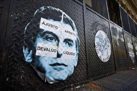Buenos Aires, Argentina - Nov 19, 2016: Poster of the Argentine President Mauricio Macri with signs in Spanish: I Cut I Press I Devaluate I Liquidate and other sticker Attention Vulture. Editorial