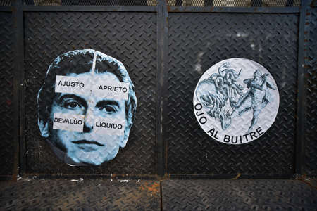 liquidate: Buenos Aires, Argentina - Nov 19, 2016: Poster of the Argentine President Mauricio Macri with signs in Spanish: I Cut I Press I Devaluate I Liquidate and other sticker Attention Vulture. Editorial