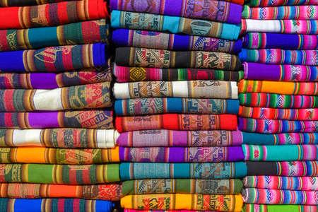 カラフルな頑丈なペルーの織物および生地の山。 写真素材