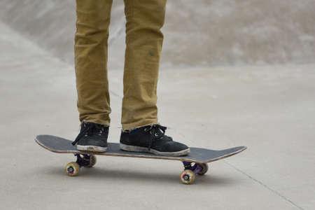 コンクリート背景とスケート ボードの足。