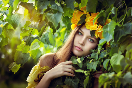 Young woman in a yellow wreath in leaves Stock Photo
