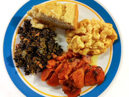 A plate of southern comfort food in America. A serving of kale greens, candied yams, macaroni and cheese, and cornbread. Top view.