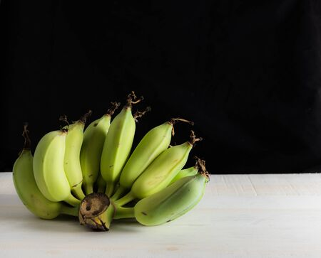 Still life bananas on white table with black background.
