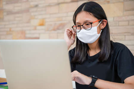 Junior high school girl Do homework at home Because the school is closed Due to the severe outbreak of the Corona virus Covid-19 and Dust PM2.5 in Bangkok Thailand