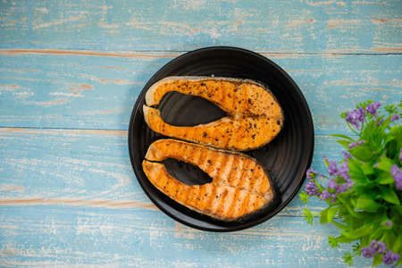 Cooked salmon steaks are prepared and served with Omega 3 Japanese food.