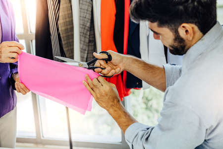 Creative Garment Design Tailoring Service Concept. Cute Professional Sewer Measuring Male Bearded Model Waist or Hip. Smiling Outfit Designer Taking Man Measurement for Formal Suit with Tape Meter Standard-Bild - 143289322
