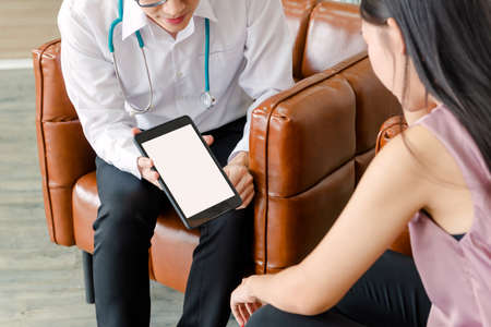 mental people concept. The young doctor's psychologist is working by tablet See reports of female mental patients at office 免版税图像 - 150292201