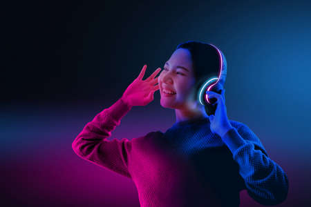 The girl is listening to the song sing with a smiling face In the studio Which has various colors of light And the pink background