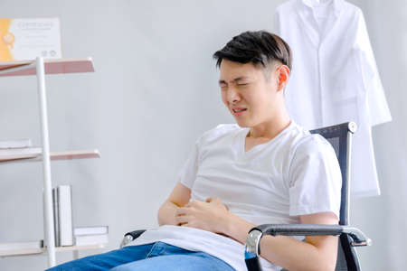 Male doctor has severe stomach pain In the office Hospital office 免版税图像