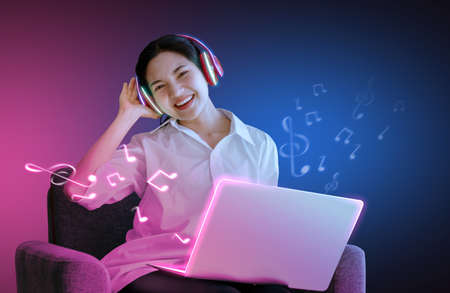 The girl is listening to the song sing with laptop on sofa, smiling face In the studio Which has various colors of light And the pink background