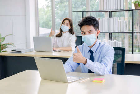 Concept corporate couple business people, businessman Confident with facemask and employees Beautiful office woman Are present talking about a new financial company's project. professional teamwork.