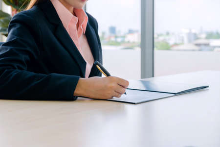 woman adult, confident smart, young business woman working in a new office Is the boss. he sign document  in a small financial company, Sign signature on paper concept.