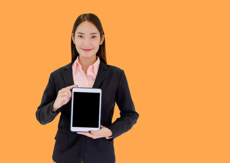 Asian businesswomen showing tablet On an orange background and free space to put text