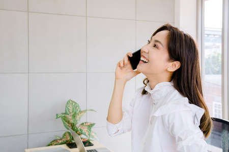 young businesswoman in office concept. she is beautiful, confident, smiling, professional corporate working in financial company Using mobile technology, tablet, cell phone, she happy and drink coffee 免版税图像 - 153296968