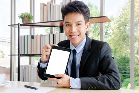 Handsome adult, confident smart, young businessman working with tablet. he used a technology smartphone, tablet, computer and relax at break time in a small financial company 免版税图像