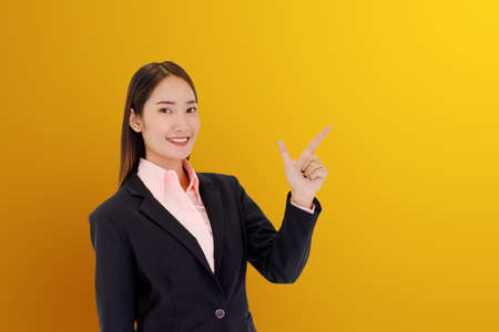 Portrait of a beautiful Asian woman pointing a finger, presenting products on a multicolored background. 免版税图像
