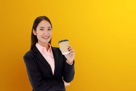 Modern corporate worker concept, beautiful young Asian woman drinking coffee. Lunch break On a yellow background And free space