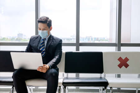A man working with a notebook Drinking coffee Sitting in a chair Waiting for a job interview During the Covid-19 Outbreak 免版税图像 - 155943786