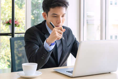 Handsome adult, confident smart, young businessman working in a new office. he used a technology smartphone, tablet, computer and relax at break time in a small financial company