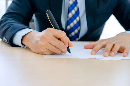 Handsome adult, confident smart, young businessman working in a new office Is the boss. he sign document  in a small financial company, Sign signature on paper concept.