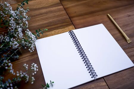 Flat lay of blank white notebook on wooden table.