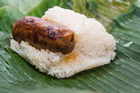 Sticky rice with thai sausage. Covered with banana leaf. Thai street food photo