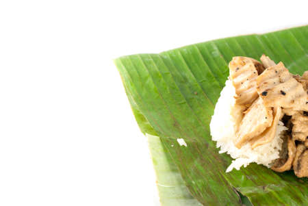 stick rice with pork wrapped in banana leaves on white background, traditional and street food in thailand photo