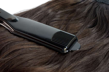 Hair straighteners and hair on white background Stock Photo - 22279220