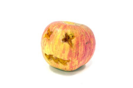Rot apple with face on white background