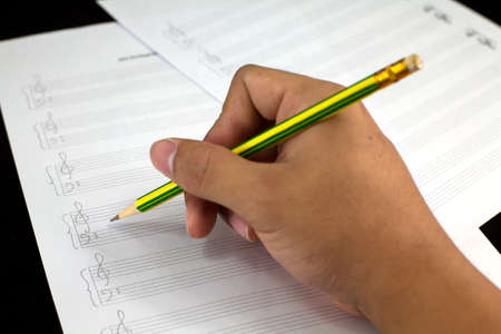 orchestration: composing musical notes on paper with pencil on black  Stock Photo