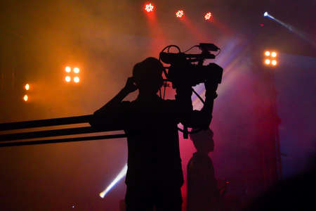 Cameraman silhouette on a concert stage Stock Photo
