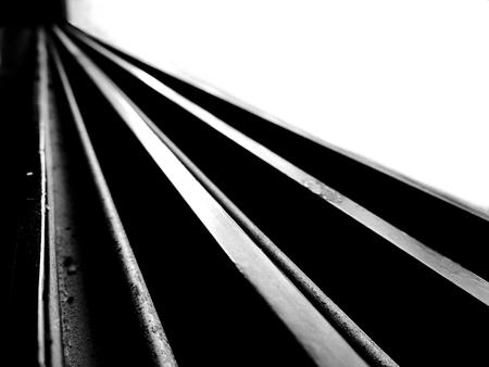 Zwart-wit beeld met hoog contrast van leidende rechte lijnen die diagonaal lopen en breed beginnen en vervolgens ver weg convergeren en een recht pad vormen met een uitgeblazen achtergrond en donkere voorgrond