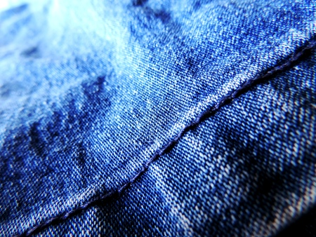Close up image of vibrant blue textured denim jeans with hem with blue stitching visible and running diagonally and gentle wrinkles and dark to bright color transitions visible Stock Photo
