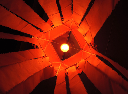 Vibrant saffron red kandeel lantern with incandescent lamp inside lantern visible with central symmetrical composition & bright orange paper tails diverging out from center outwards, bottom up view Stockfoto