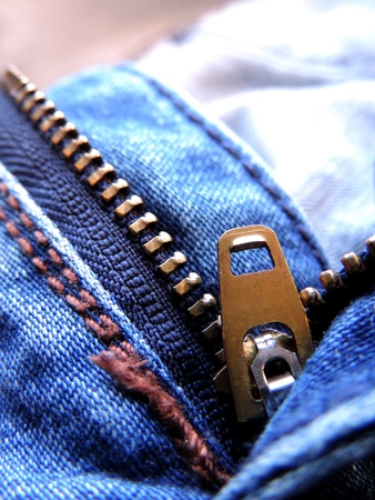 Close up image of a blue denim jeans with its metal zipper or fly open and zipper tape metallic puller, bridge, slider body and chain visible along with brown stitching