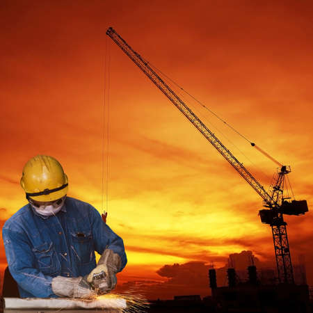 Construction worker cutting metal with a construction background. photo