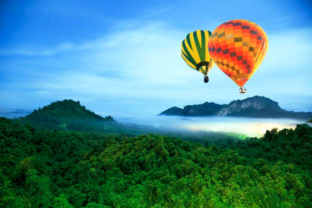 Colorful hot-air balloons flying over the mountain photo